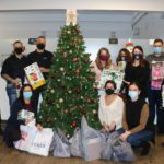 The NORPRO family gathered around the Christmas tree with our donations.